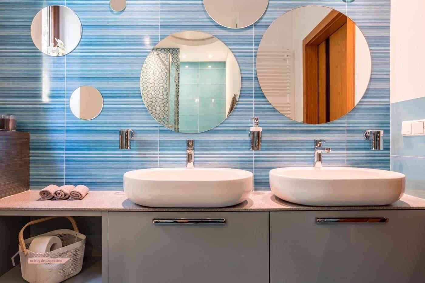 Baño con dos lavabos y espejos redondos