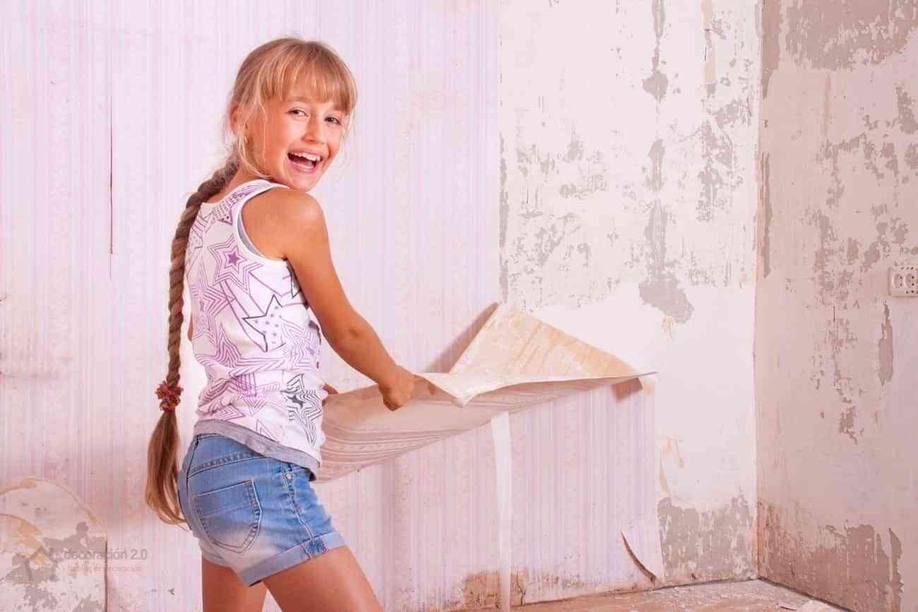 chica se divierte quitando papel pintado pared
