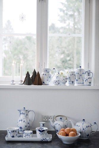 ventana decorada con árboles de Navidad y vajilla