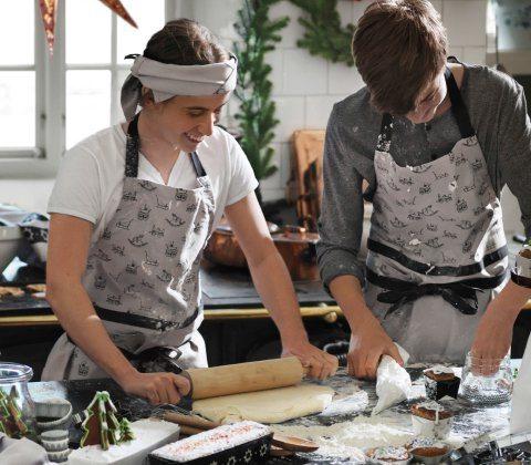 dos personas cocinando con delantales grises